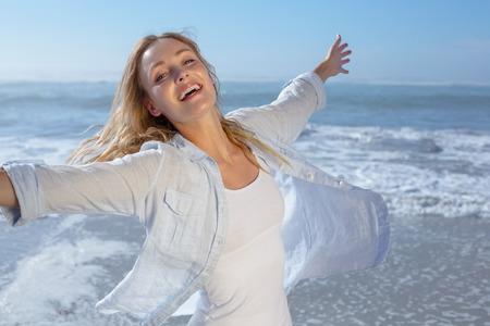 mujeres felices: Hermosa rubia extendiendo los brazos en la playa en un día soleado