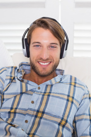 Casual smiling man lying on couch listening to music at home in the living room photo