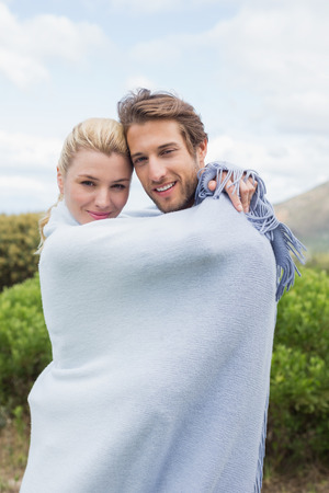 hair wrapped up: Cute smiling couple standing outside wrapped in blanket on a chilly day Stock Photo