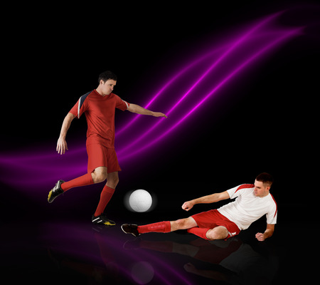 Football players tackling for the ball on black background with lights Stock Photo - 29053486