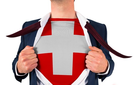 Businessman opening shirt to reveal swiss flag on white background photo