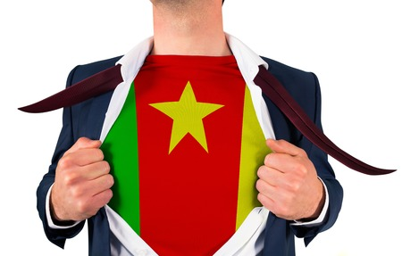 Businessman opening shirt to reveal cameroon flag on white background Stock Photo