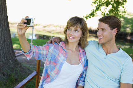 Cute couple sitting on bench in the park taking a selfie on a sunny day photo