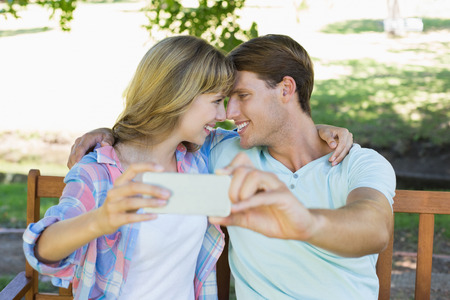 Smiling couple sitting on bench in the park taking a selfie on a sunny day photo