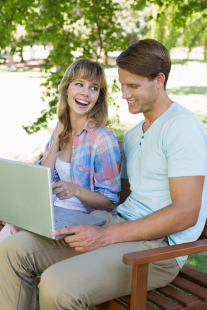 Cute young couple sitting on park bench using laptop on a sunny day photo