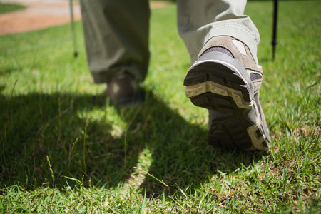 adventuring: Womans feet in hiking boots walking on grass on a sunny day Stock Photo