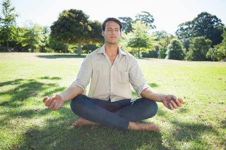 Stylish man meditating in the park on a sunny day photo