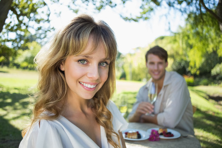 Cute blonde smiling at camera with boyfriend in background on a sunny day photo
