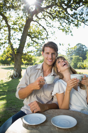 Laughing couple having tea outside in a cafe on a sunny day photo