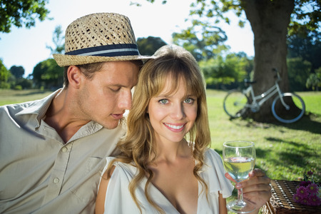 Cute couple drinking white wine on a picnic woman smiling at camera on a sunny day photo