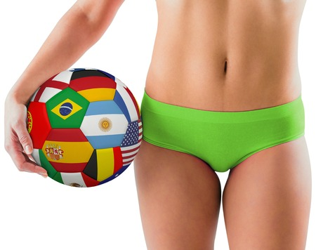 Fit girl in green bikini holding flag football on white background photo