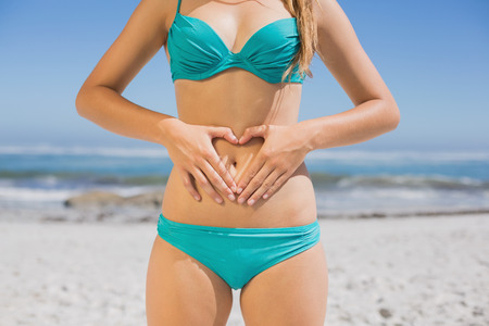 Fit woman in bikini on the beach making heart shape on stomach on a sunny day photo