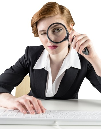 Redhead businesswoman looking through magnifying glass on white background Stock Photo - 29045527