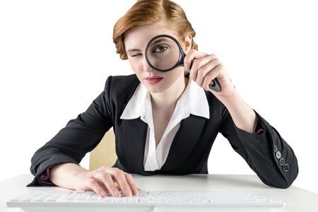 Redhead businesswoman looking through magnifying glass on white background Stock Photo - 29054595