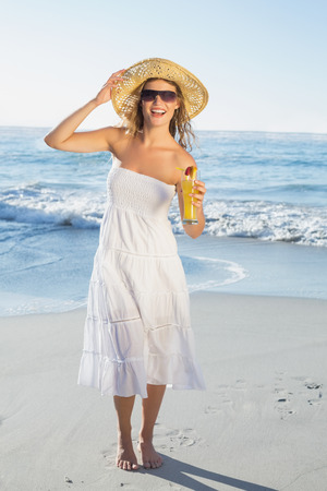 Beautiful blonde in white sundress on the beach with cocktail on a sunny day photo