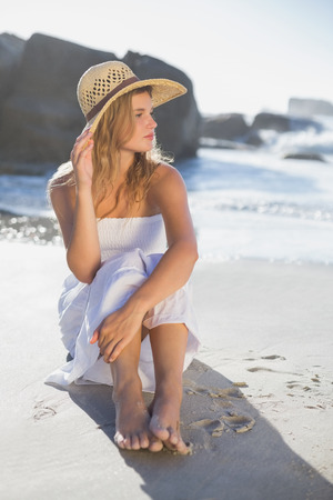 Beautiful smiling blonde in sundress sitting on the beach on a sunny day photo