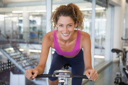 Pretty fit woman on the spin bike smiling at camera at the gym photo