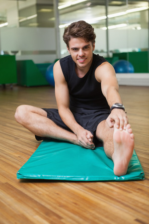 touching toes: Fit smiling man warming up in fitness studio at the gym Stock Photo