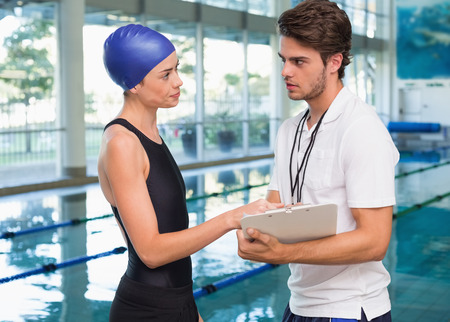 Swimmer discussing times with her coach by the pool at the leisure center photo