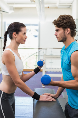 Fit focused couple exercising with blue dumbbells at the gym photo