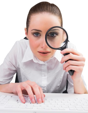 Businesswoman typing and looking through magnifying glass on white background Stock Photo - 29045510