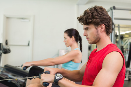 man working out: Hombre Focused que se resuelve en la m�quina de remo en el gimnasio Foto de archivo