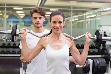 Fit smiling woman lifting barbell with her trainer at the gym photo