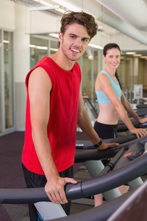 Smilng man and woman on the treadmills at the gym photo