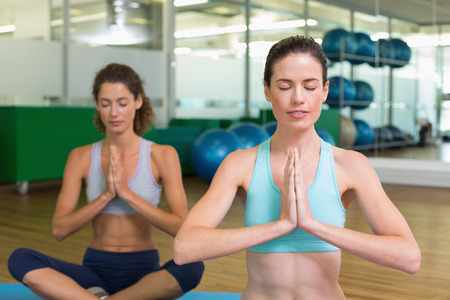 Fit women doing yoga together in studio at the gym photo