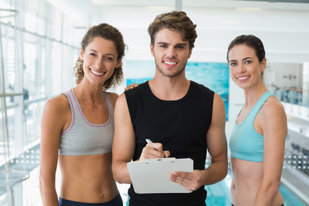 noting: Fit women with trainer taking notes and smiling at camera at the gym