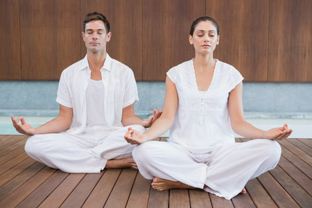 Attractive couple in white meditating in lotus pose in health spa photo