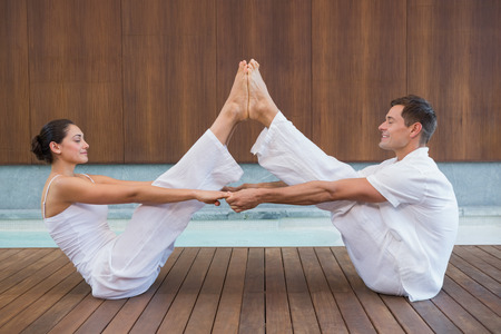 Peaceful couple sitting in boat position together in health spa photo