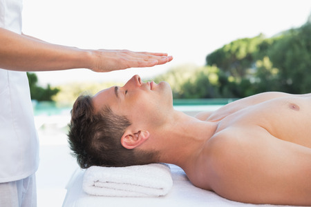 heal care: Peaceful man getting reiki treatment poolside outside at the spa Stock Photo