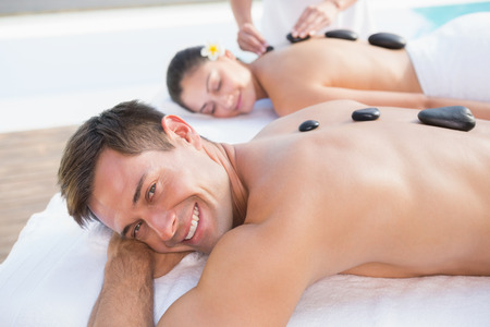 Attractive couple enjoying hot stone massage poolside outside at the spa photo