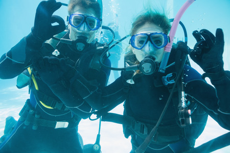 scuba woman:  Friends on scuba training submerged in swimming pool looking to camera on their holidays