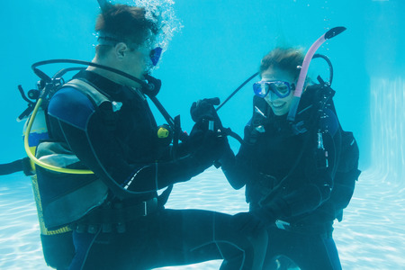 Man proposing marriage to his shocked girlfriend underwater in scuba gear on their holidays photo