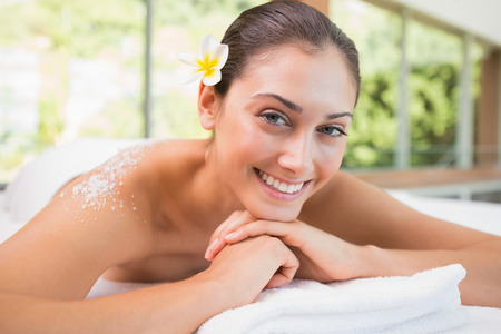body scrub: Beautiful smiling brunette lying on massage table with salt scrub on back in the health spa Stock Photo