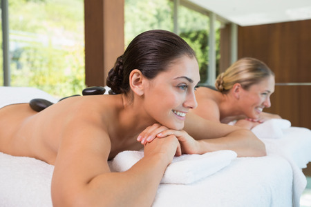 Happy friends lying on massage tables with hot stones on\ their backs in the health spa