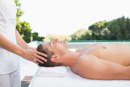 Peaceful man getting a head massage poolside outside at the spa photo