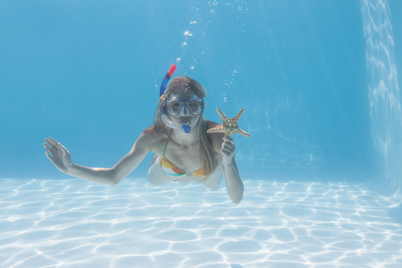 Cute blonde underwater in the swimming pool with snorkel and starfish on their holidays photo