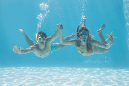 escapism: Cute couple underwater in the swimming pool with snorkel and starfish on their holidays