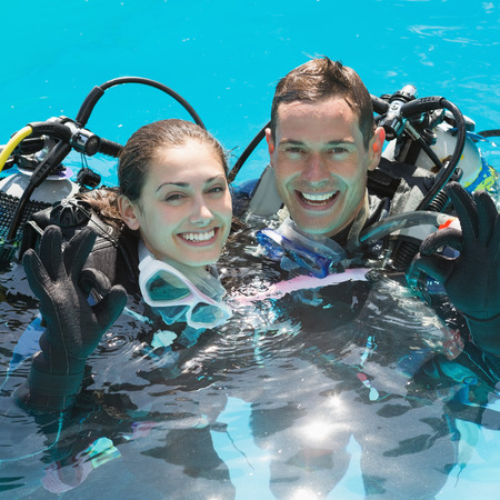 Smiling couple on scuba training in swimming pool showing ok gesture on a sunny day photo