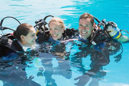 convivialit�: Sourire amis sur la formation de plong�e en piscine sur une journ�e ensoleill�e Banque d'images