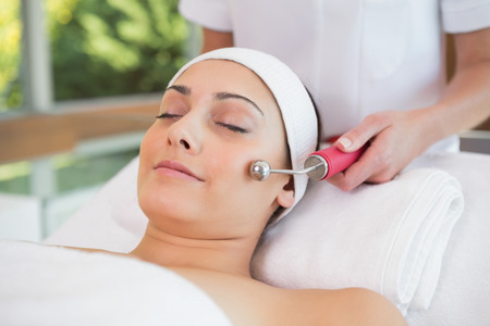 Peaceful brunette getting micro dermabrasion in the health spa photo