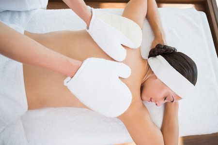 mitts: Beauty therapist rubbing womans back with heated mitts in the health spa