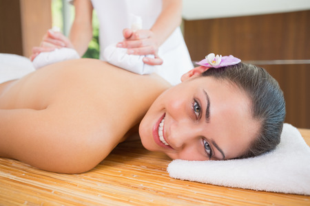 Smiling woman getting a back massage with herbal compresses\ in the health spa
