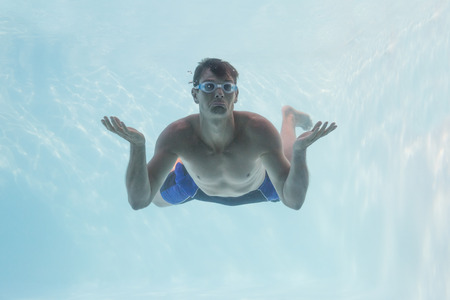 shrugging: Man shrugging shoulders underwater in swimming pool on his holidays