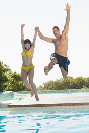 Excited couple jumping into swimming pool on holidays on a sunny day photo