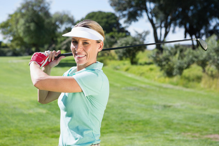 Female golfer taking a shot and smiling at camera on a sunny day at the golf course photo