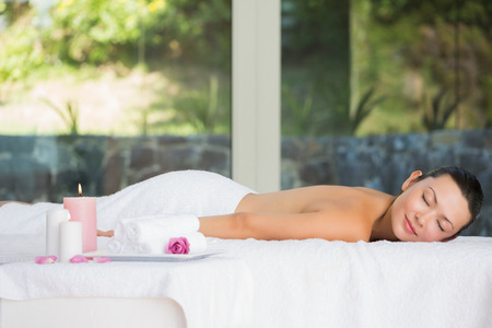 Smiling brunette lying on massage table with eyes closed at the spa photo